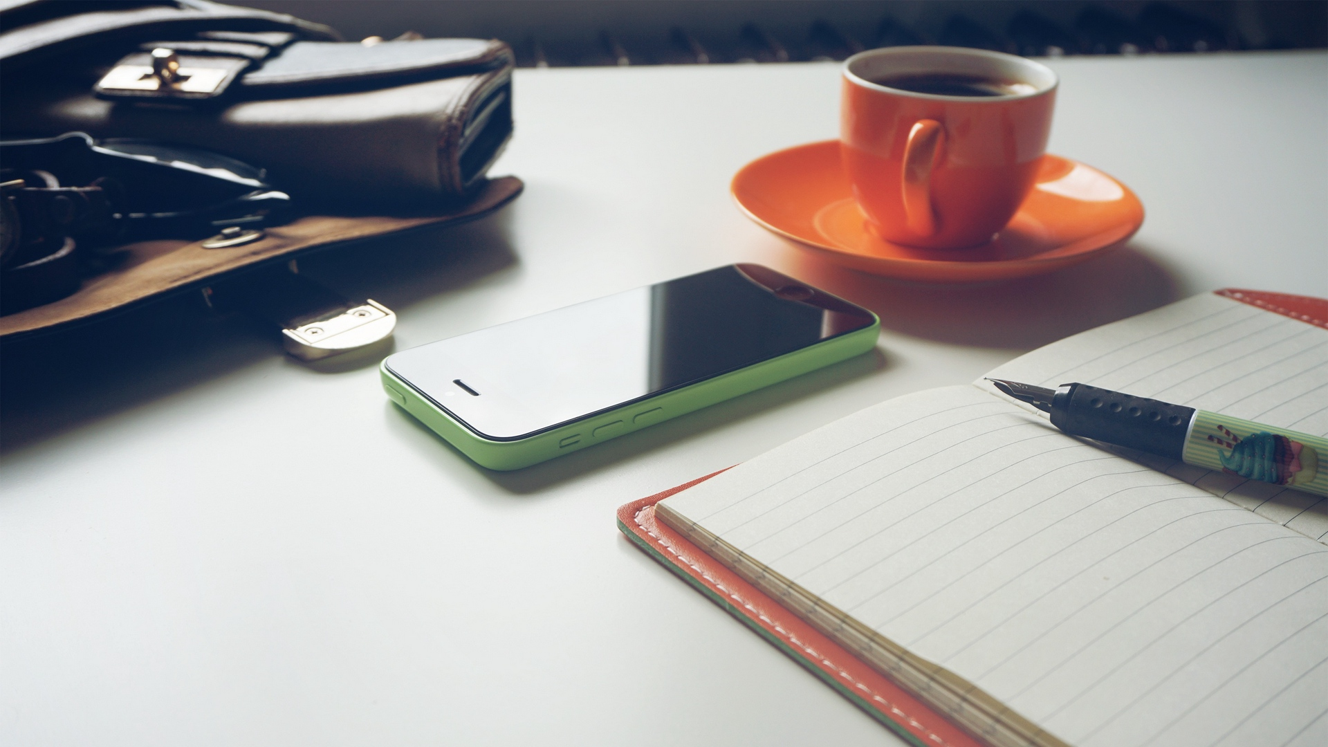 cell phone, cup of coffee and notebook