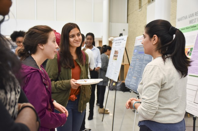 students chatting at a poster presentation