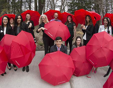 sloan students with red umbrellas