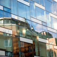 Martha Van Rensselaer Hall reflected in the outer facade of the Human Ecology Building