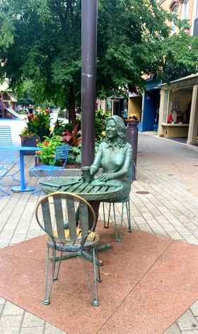 statue on ithaca commons of a girl with a cup seated at a table