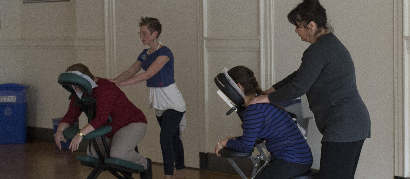 Two staff members receiving a chair massage