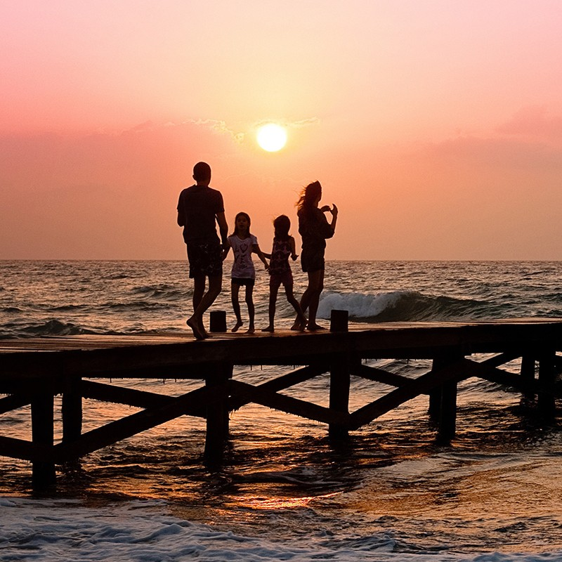 family by the sea at sunset