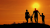 Family running on hilltop in sunset setting